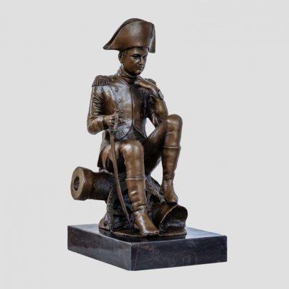 Statue de Napoléon en bronze le représentant assis sur un canon